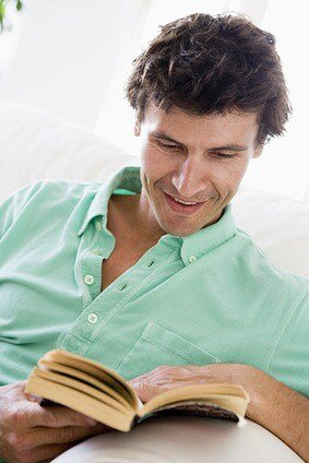 Man reading book in living room smiling