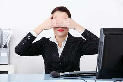 Businesswoman at office covering her eyes.