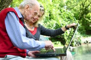 Old man and young women using computer