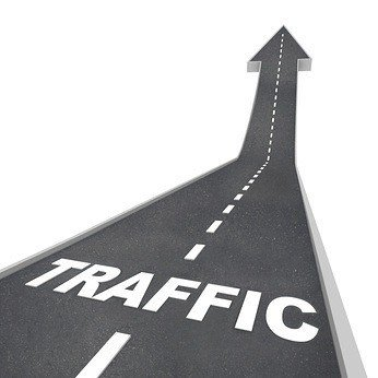 The word Traffic on a road rising up to represent increased activity on the web or transportation system such as freeways and highways