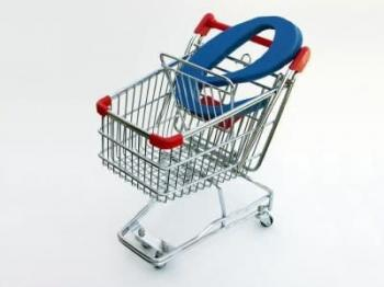 "A miniature shopping cart isolated on white with a blue letter ""E"" in the basket depicting e-commerce or online shopping."