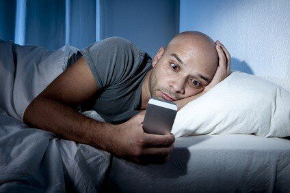Man checking email in bed