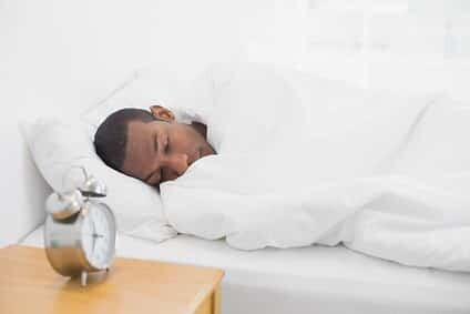 Young man sleeping in bed with alarm clock in foreground at bedroom