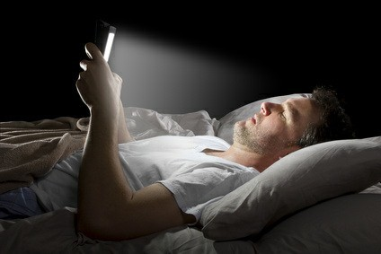 Man reading emails in bed