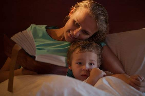 Mum reading bedtime story to child